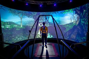A traumatic brain injury patient walks through a virtual reality scenario at the Computer Assisted Rehabilitation Environment Laboratory at National Intrepid Center of Excellence at Walter Reed National Military Medical Center in Bethesda, Md., March 20, 2017. The patient is attached to a safety harness and walks on a treadmill on a platform that moves and rotates in conjunction with movements of the projected environment. Motion capture cameras track the patient's movements via reflective markers that are applied to the patient and supply data on physical deficits to physical therapists. (U.S. Air Force photo by J.M. Eddins Jr.)